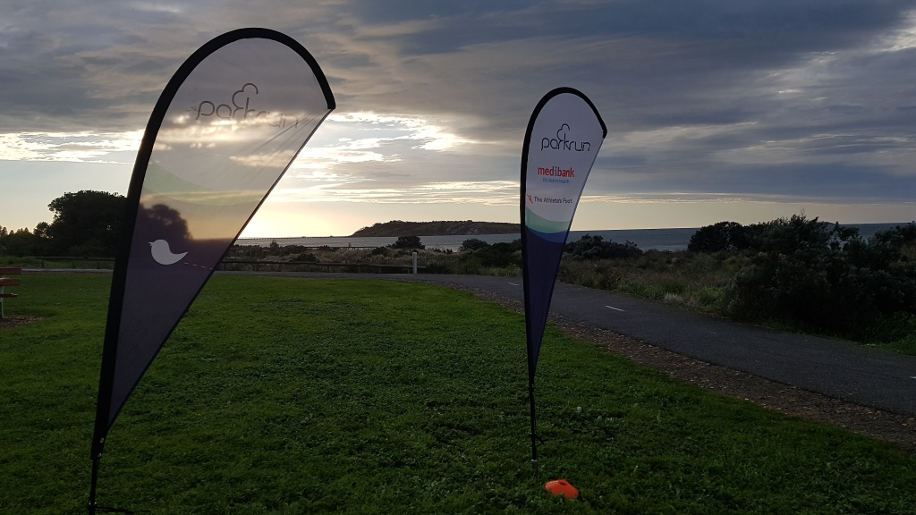 Photo of 2 parkrun flags with path and ocean in the background